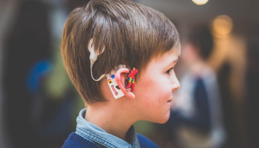 anak menggunakan alat bantu dengar